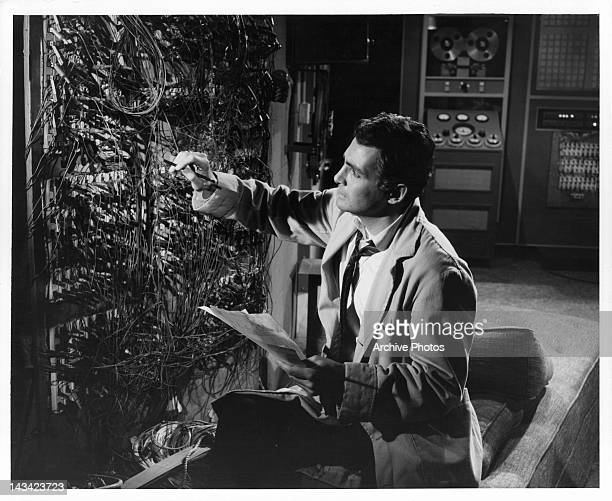 David Hedison noting wires in back of large computer in a scene from the film 'The Fly' 1958