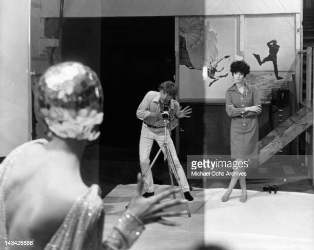 David Hemmings directs the pose of a model in a scene from the film 'Blow Up' 1966