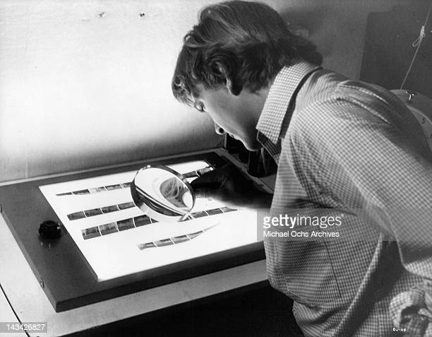 David Hemmings examines the negative of a photograph with a magnifying glass in a scene from the film 'Blow Up' 1966