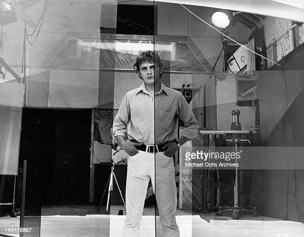 David Hemmings looks meditative through the five large transparencies he is going to us for a fashion session in a scene from the film 'Blow Up' 1966