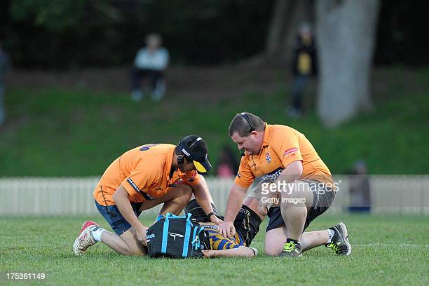 David Hickey receives treatment from medics after cloapsing while leaving the field during the round 16 Shute Shield match between Sydney Uni and...