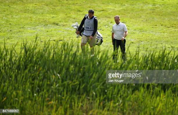 David Higgins of the Great Britain and Ireland PGA Cup team makes his way to the green with his caddy during the morning fouball matches on day 1 of...