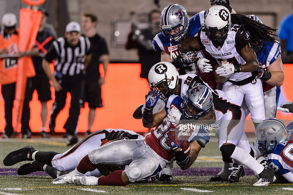 David Hinds #20 of the Ottawa Redblacks tackles Tyrell Sutton #20 of the Montreal Alouettes during the CFL game at Percival Molson Stadium on June 25, 2015 in Montreal, Quebec, Canada. The Ottawa Redblacks defeated the Montreal Alouettes 20-16.