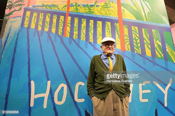 David Hockney poses at the Taschen stand in front of a giant poster at the 2016 Frankfurt Book Fair on October 19 2016 in Frankfurt am Main Germany...