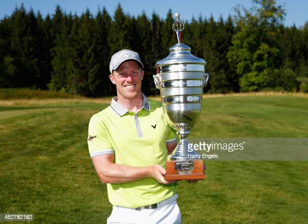 David Horsey of England celebrates with the trophy after winning the final round of the M2M Russian Open at Tseleevo Golf Polo Club on July 27 2014...