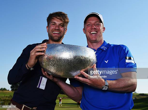 David Horsey of England holds the trophy with his manager John Muff after winning the Made in Denmark at Himmerland Golf Spa Resort on August 23 2015...