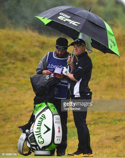 David Horsey of England shelters from the rain on the 2nd tee during Day Three of the AAM Scottish Open at Dundonald Links Golf Course on July 15...