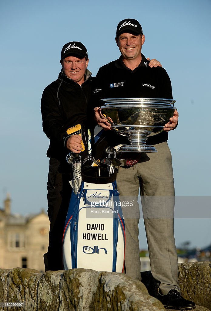 David Howell of England celebrates with the trophy and his caddy Steve Brotherhood on the Swilken Bridge on the 18th hole after victory at the Alfred Dunhill Links Championship on The Old Course, at St Andrews on September 29, 2013 in St Andrews, Scotland. Howell won after the second playoff hole against Peter Uihlein.