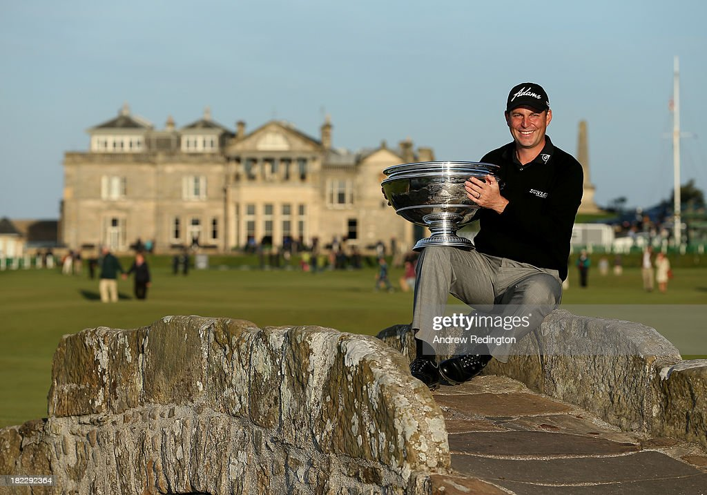 David Howell of England celerbrates with the trophy on the Swilken Bridge on the 18th hole after victory at the Alfred Dunhill Links Championship on The Old Course, at St Andrews on September 29, 2013 in St Andrews, Scotland. Howell won after the second playoff hole against Peter Uihlein.