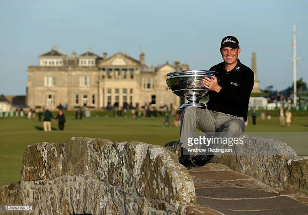 David Howell of England celerbrates with the trophy on the Swilken Bridge on the 18th hole after victory at the Alfred Dunhill Links Championship on...