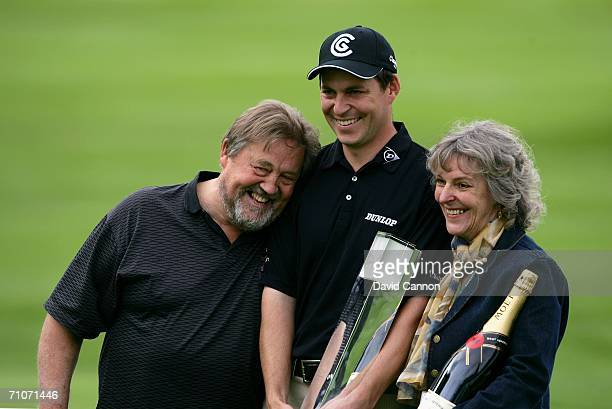 David Howell of England poses with his parents and the trophy following his victory in the Final Round of the BMW Championship at The Wentworth Club...
