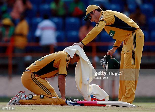 David Hussey puts a towel over the head of Shane Watson of Australia as he collapses to his knees for a water break during the OneDay International...