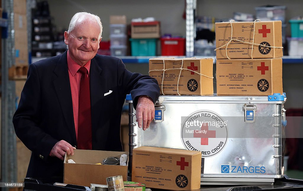David Isherwood poses for a photograph beside replica Red Cross parcels similar to the ones he received as a boy, inside the Red Cross Bristol Emergency Response Unit Warehouse, to mark the 150th anniversary of The Red Cross movement on October 15, 2013 in Bristol, England. The 80-year-old Channel Islands resident - who as a survivor of the German occupation during WW2 was kept alive by food parcels he received - travelled to the British Red Cross Bristol Emergency Response Unit to celebrate the 25 million food parcels issued worldwide by the British Red Cross.