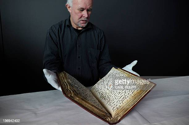 David Jacobs senior conservator at the British Library poses for photographers with one of the oldest known copies of the Koran at the British Museum...