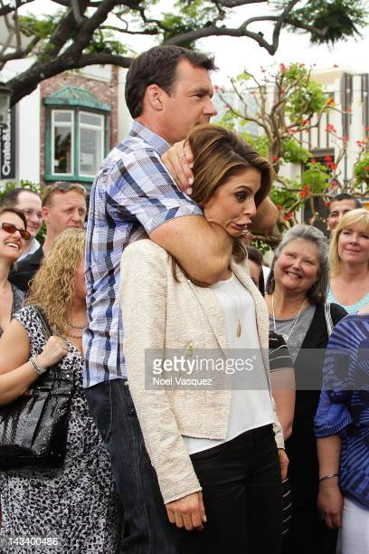 David James Elliott demonstrates a choke hold on Maria Menounos at 'Extra' at The Grove on April 25 2012 in Los Angeles California