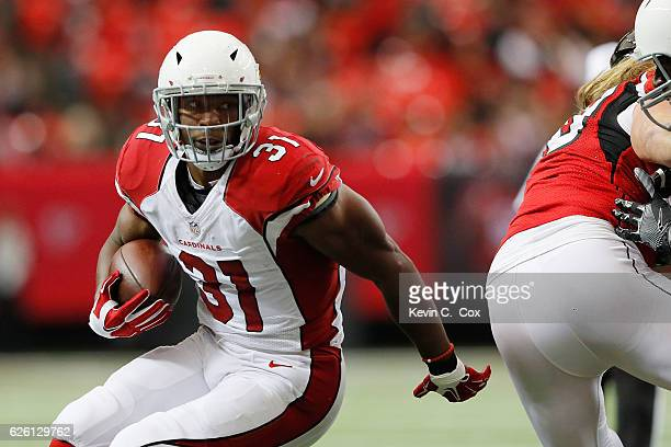 David Johnson of the Arizona Cardinals runs the ball during the first half against the Atlanta Falcons at the Georgia Dome on November 27 2016 in...