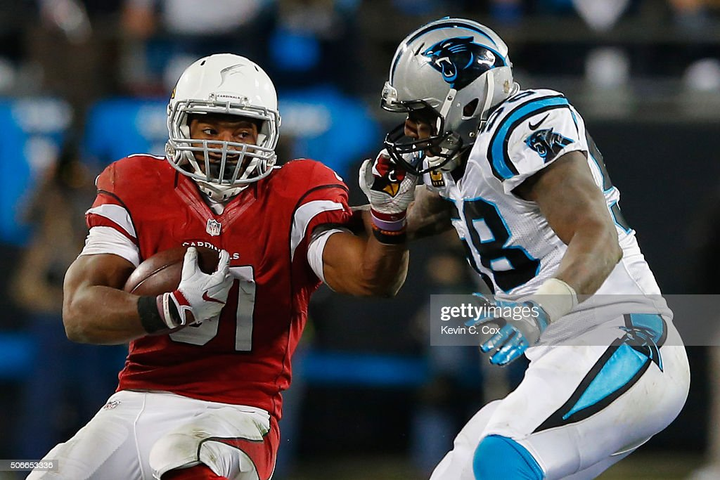 David Johnson of the Arizona Cardinals runs with the ball in the first half as Thomas Davis of the Carolina Panthers defends him during the NFC...