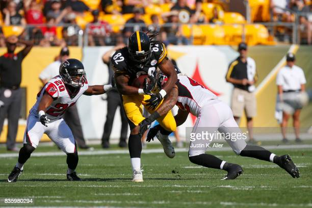 David Johnson of the Pittsburgh Steelers runs after the catch against Sharrod Neasman and Duke Riley of the Atlanta Falcons during a preseason game...