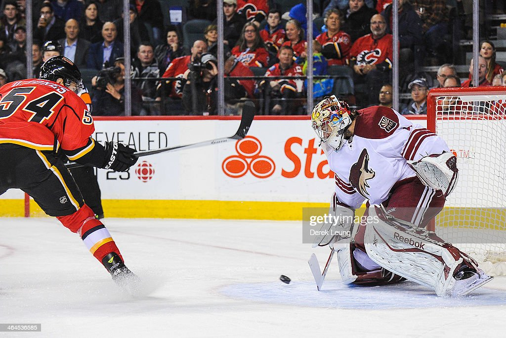 David Jones #54 of the Calgary Flames makes an attempt on Mike Smith #41 of the Phoenix Coyotes during an NHL game at Scotiabank Saddledome on January 22, 2014 in Calgary, Alberta, Canada. The Flames defeated the Coyotes 3-2.