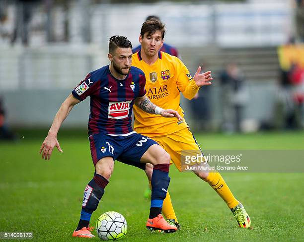 David Junca of SD Eibar duels for the ball with Lionel Messi of FC Barcelona during the La Liga match between SD Eibar and FC Barcelona at Ipurua...