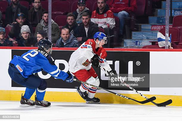 David Kase of Team Czech Republic skates the puck against Miro Heiskanen of Team Finland during the IIHF World Junior Championship preliminary round...