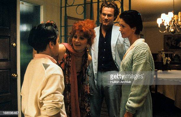 David Keith and Cyndi Lauper observing child near door in a scene from the film 'Off And Running' 1991