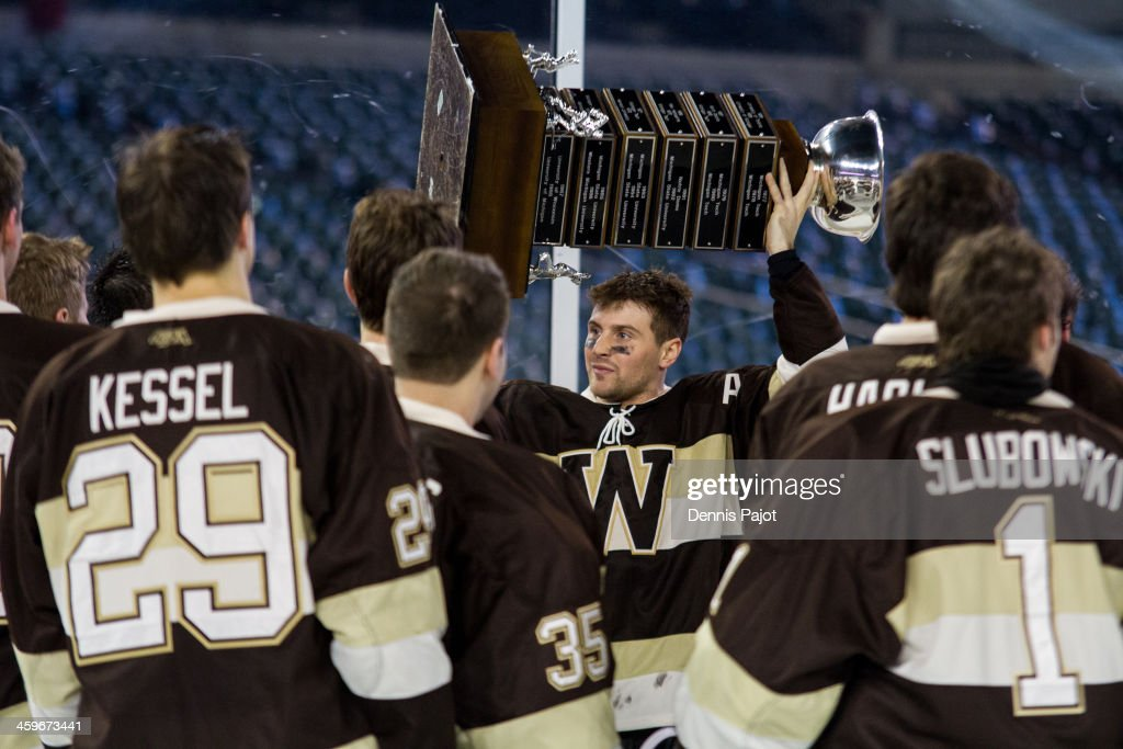 David Killip #18 of the Western Michigan Broncos hoists the MacInnes cup after a 1-0 overtime win in the championship game over the Michigan Tech Huskies on December 28, 2013 at Comerica Park in Detroit, Michigan.
