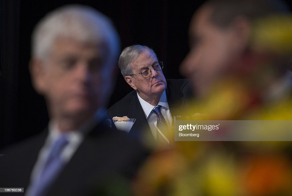 David Koch, executive vice president of chemical technology for Koch Industries Inc., center, listens as Ben S. Bernanke, chairman of the U.S. Federal Reserve, unseen, speaks to the Economic Club of New York in New York, U.S., on Tuesday, Nov. 20, 2012. Bernanke said that an agreement on ways to reduce long-term federal budget deficits could remove an impediment to growth, while failure to avoid the so-called fiscal cliff would pose a 'substantial threat' to the recovery. Photographer: Scott Eells/Bloomberg via Getty Images