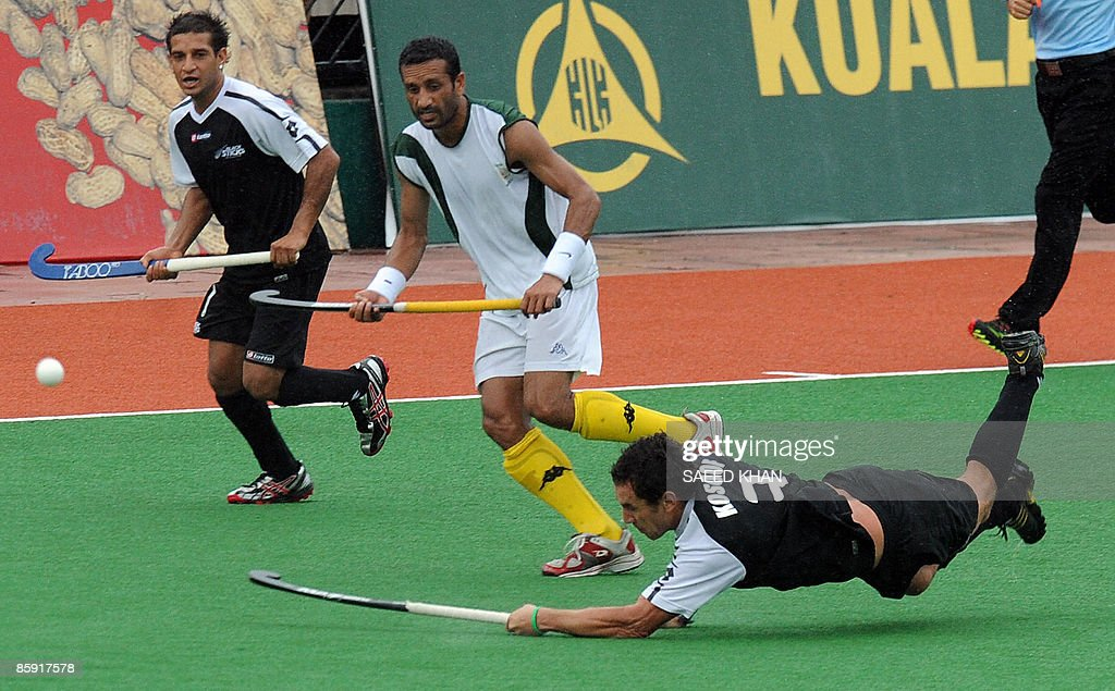 David Kossof of New Zealand dives in an attempt to chop the ball into the goal post as Dilawar Hussain of Pakistan defends during the third and...