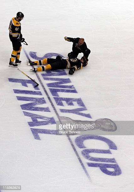 David Krejci of the Boston Bruins and a member of the staff check on Nathan Horton after being check by Aaron Rome of the Vancouver Canucks during...