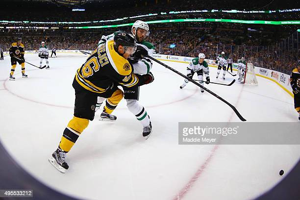 David Krejci of the Boston Bruins and Jyrki Jokipakka of the Dallas Stars battle for the puck during the first period at TD Garden on November 3 2015...