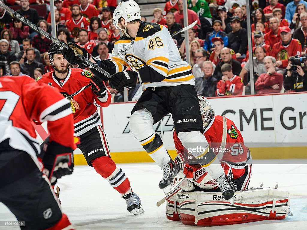 David Krejci #46 of the Boston Bruins attempts to get out of the way of the puck in front of goalie Corey Crawford #50 as Niklas Hjalmarsson #4 of the Blackhawks watches from behind in Game Two of the Stanley Cup Final at the United Center on June 15, 2013 in Chicago, Illinois.