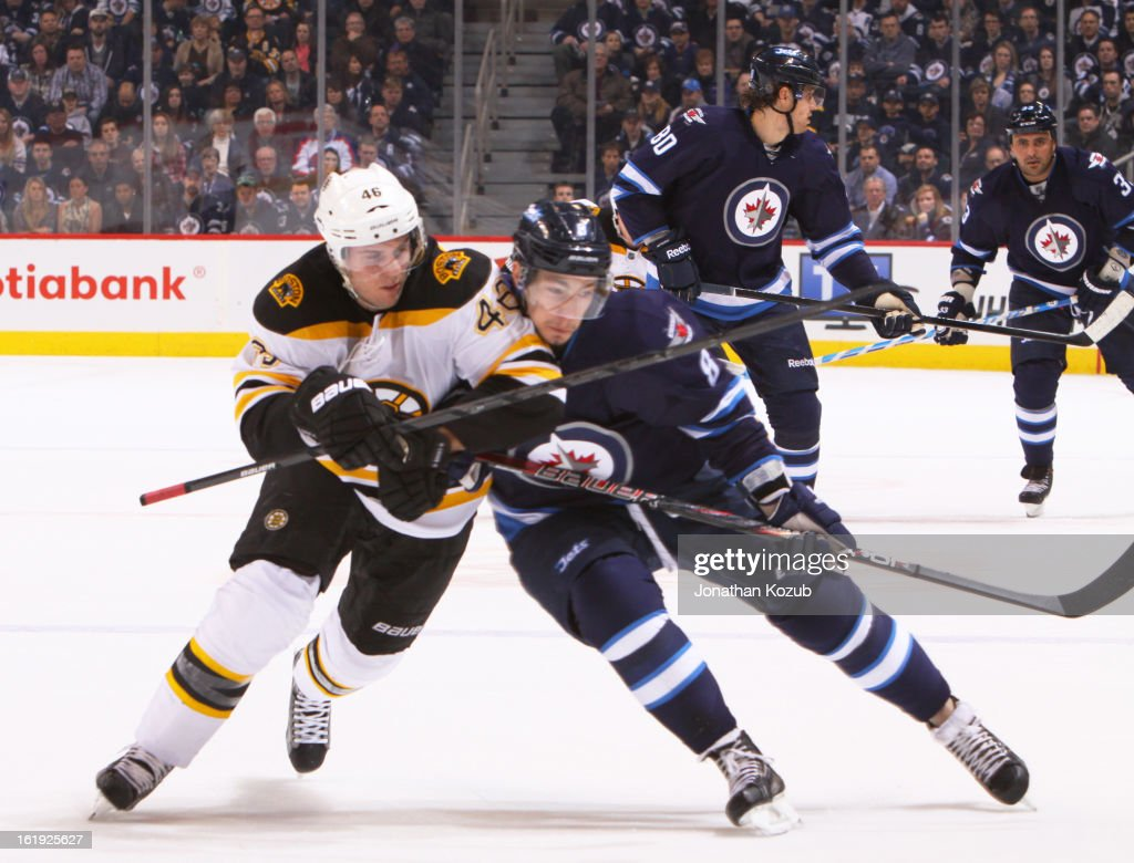 David Krejci #46 of the Boston Bruins battles Alexander Burmistrov #8 of the Winnipeg Jets as they follow the play up the ice during first period action at the MTS Centre on February 17, 2013 in Winnipeg, Manitoba, Canada.