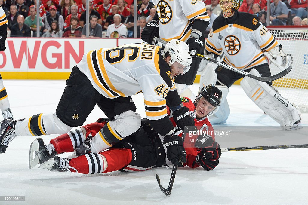 David Krejci #46 of the Boston Bruins falls onto Jonathan Toews #19 of the Chicago Blackhawks in Game One of the Stanley Cup Finals at the United Center on June 12, 2013 in Chicago, Illinois.