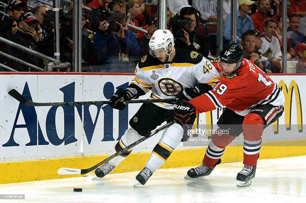 David Krejci #46 of the Boston Bruins fights for control of the puck against Jonathan Toews #19 of the Chicago Blackhawks in Game Two of the NHL 2013 Stanley Cup Final at United Center on June 15, 2013 in Chicago, Illinois. The Bruins won 2-1 in overtime.