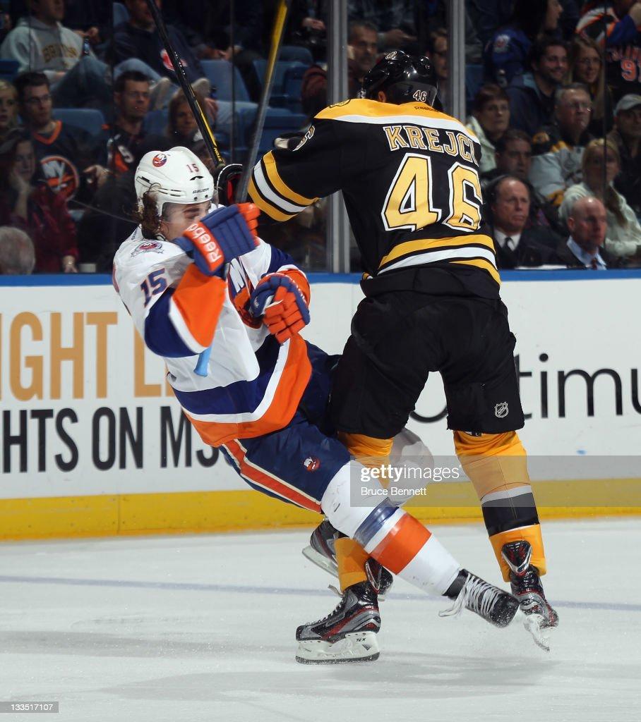 David Krejci of the Boston Bruins hits PA Parenteau of the New York Islanders at the Nassau Veterans Memorial Coliseum on November 19 2011 in...