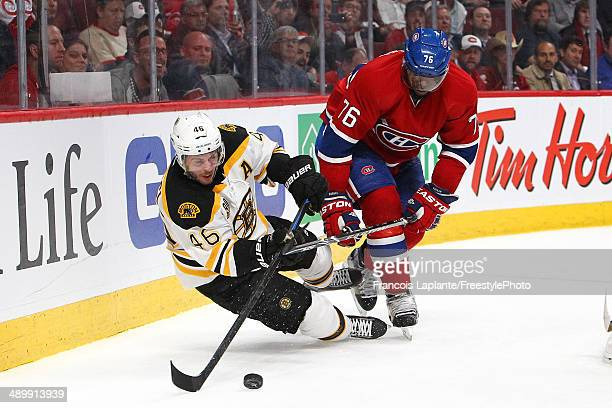David Krejci of the Boston Bruins passes the puck as he falls to the ice against PK Subban of the Montreal Canadiens in Game Six of the Second Round...