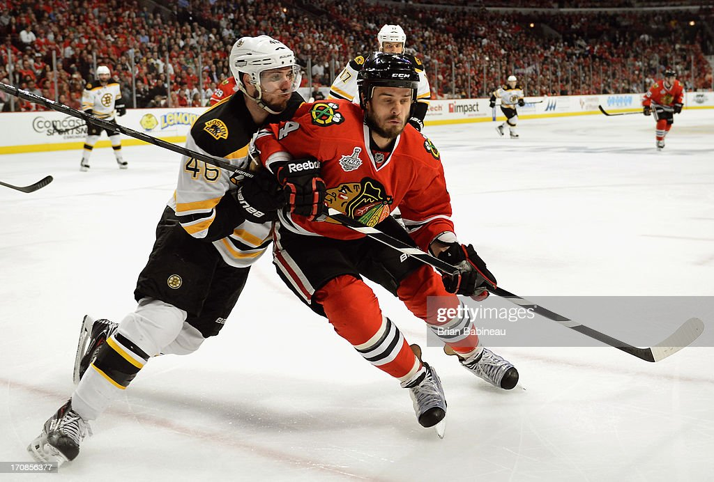 David Krejci #46 of the Boston Bruins pushes Niklas Hjalmarsson #4 of the Chicago Blackhawks during the first period of Game Two of the 2013 Stanley Cup Final at the United Center on June 15, 2013 in Chicago, Illinois.