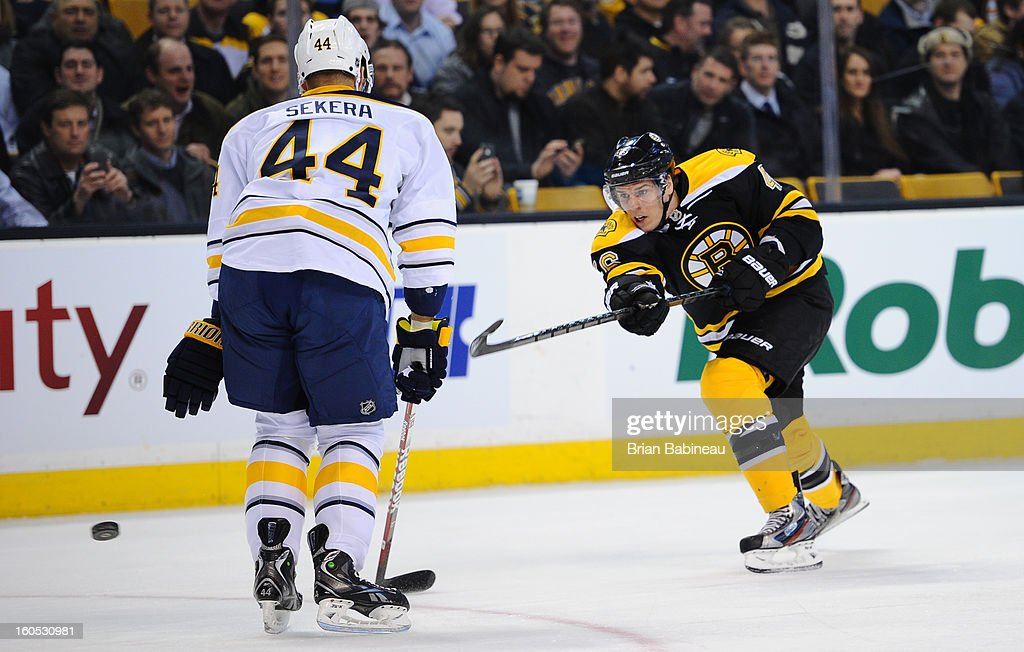 David Krejci #46 of the Boston Bruins shoots the puck against Andrej Sekera #44 of the Buffalo Sabres at the TD Garden on January 31, 2013 in Boston, Massachusetts.