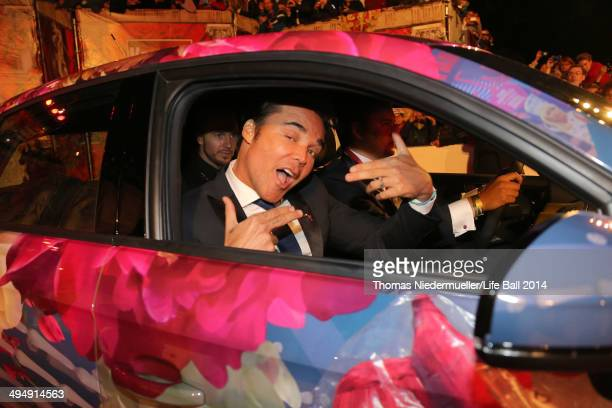David LaChapelle poses in an audi car designed by himself as he attends the Life Ball 2014 Magenta Carpet Arrivals at City Hall on May 31 2014 in...