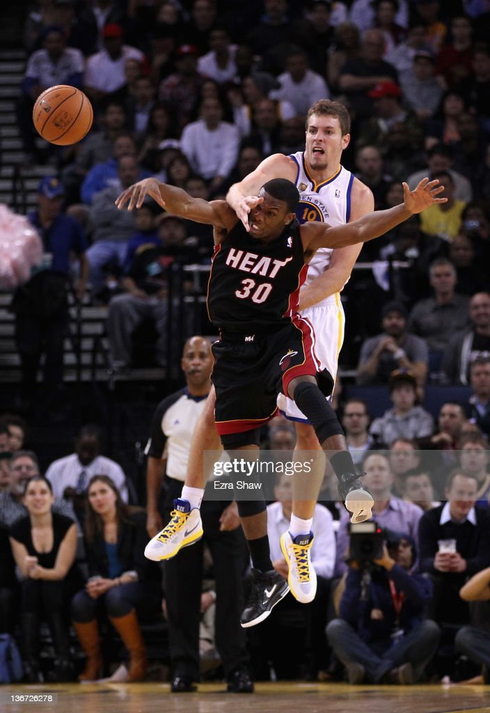 David Lee #10 of the Golden State Warriors and Norris Cole #30 of the Miami Heat go for a loose ball at Oracle Arena on January 10, 2012 in Oakland, California.