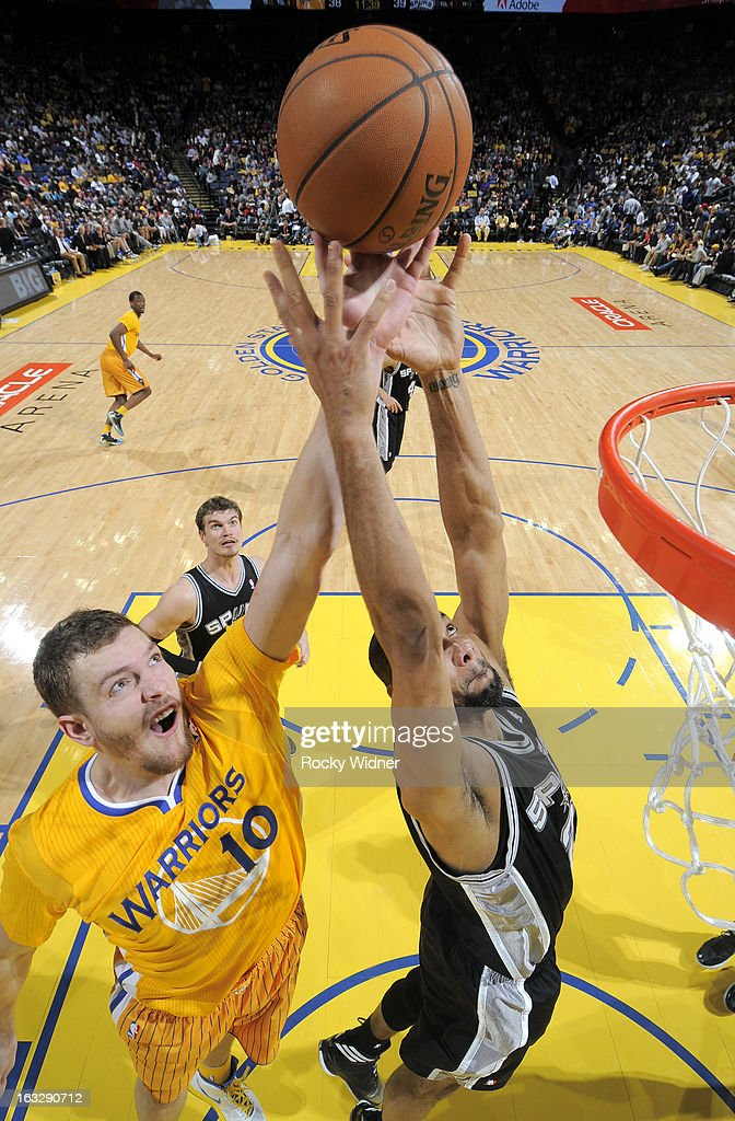 David Lee #10 of the Golden State Warriors and Tim Duncan #21 of the San Antonio Spurs battle for the rebound on February 22, 2013 at Oracle Arena in Oakland, California.