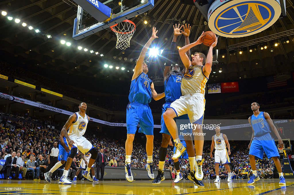 David Lee #10 of the Golden State Warriors attempts to shoot the ball over <a gi-track='captionPersonalityLinkClicked' href=/galleries/search?phrase=Dirk+Nowitzki&family=editorial&specificpeople=201490 ng-click='$event.stopPropagation()'>Dirk Nowitzki</a> #41 and <a gi-track='captionPersonalityLinkClicked' href=/galleries/search?phrase=Ian+Mahinmi&family=editorial&specificpeople=740196 ng-click='$event.stopPropagation()'>Ian Mahinmi</a> #28 of the Dallas Mavericks on April 12, 2012 at Oracle Arena in Oakland, California.