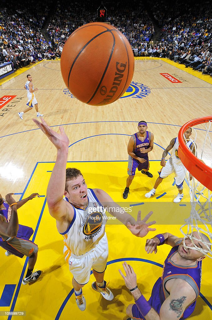 David Lee #10 of the Golden State Warriors flips up a shot over <a gi-track='captionPersonalityLinkClicked' href=/galleries/search?phrase=Marcin+Gortat&family=editorial&specificpeople=589986 ng-click='$event.stopPropagation()'>Marcin Gortat</a> #4 of the Phoenix Suns on February 7, 2011 at Oracle Arena in Oakland, California.