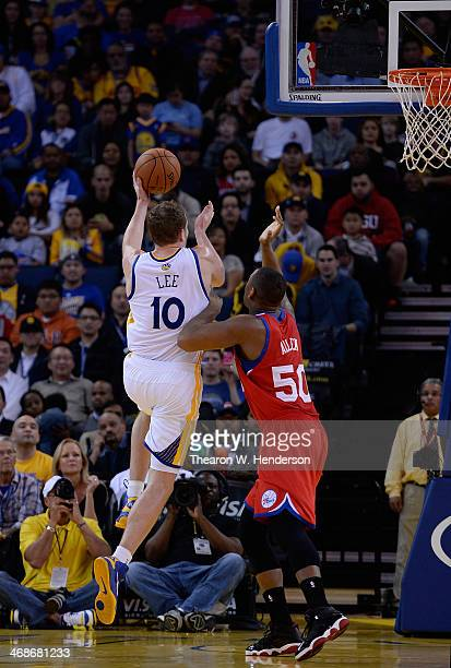 David Lee of the Golden State Warriors goes in for a layup over Lavoy Allen of the Philadelphia 76ers at ORACLE Arena on February 10 2014 in Oakland...