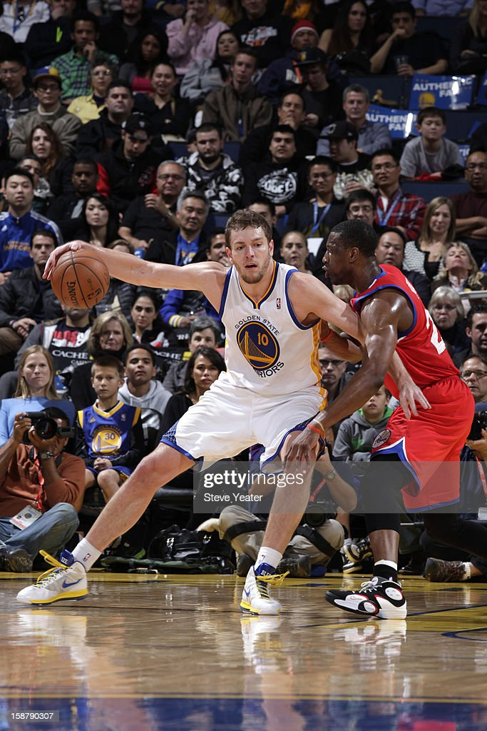David Lee #10 of the Golden State Warriors posts-up against Thaddeus Young #21 of the Philadelphia 76ers on December 28, 2012 at Oracle Arena in Oakland, California.