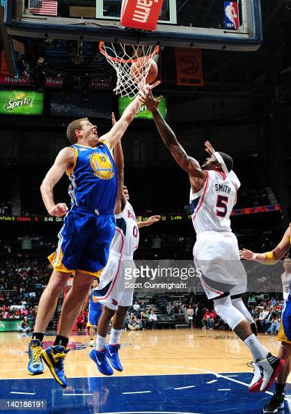 David Lee of the Golden State Warriors shoots a layup against Josh Smith of the Atlanta Hawks on February 29 2012 at Philips Arena in Atlanta Georgia...