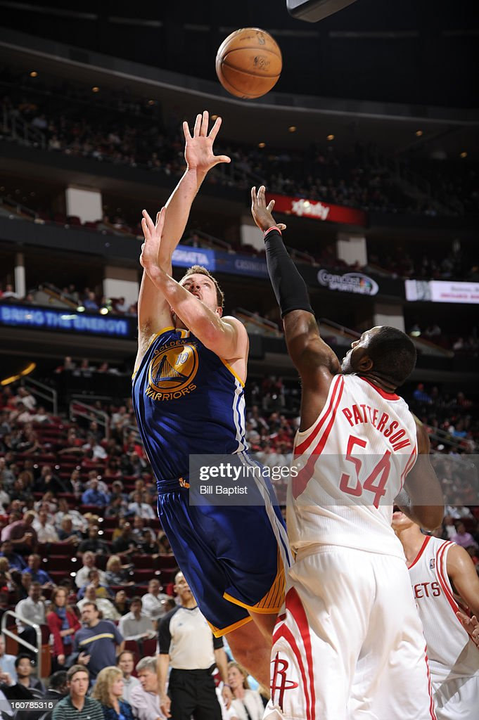 David Lee #10 of the Golden State Warriors shoots against Patrick Patterson #54 of the Houston Rockets on February 5, 2013 at the Toyota Center in Houston, Texas.