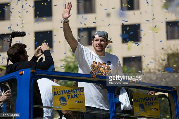 David Lee of the Golden State Warriors waves to the crowd during the Golden State Warriors Victory Parade in Oakland California Thousands are...