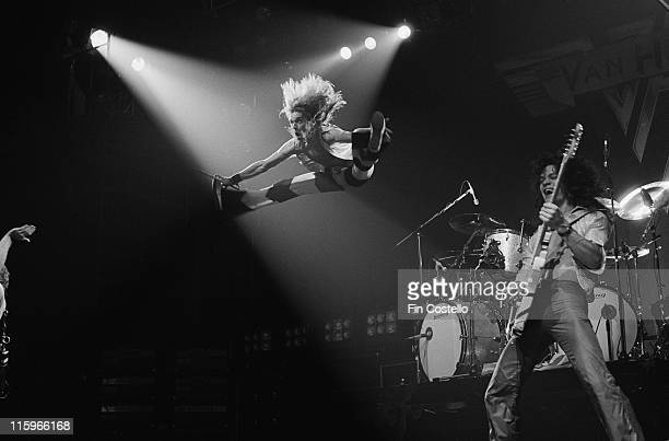 David Lee Roth singer with Van Halen jumping in midair alongside guitarist Eddie Van Halen during a live concert performance by the US rock band at...